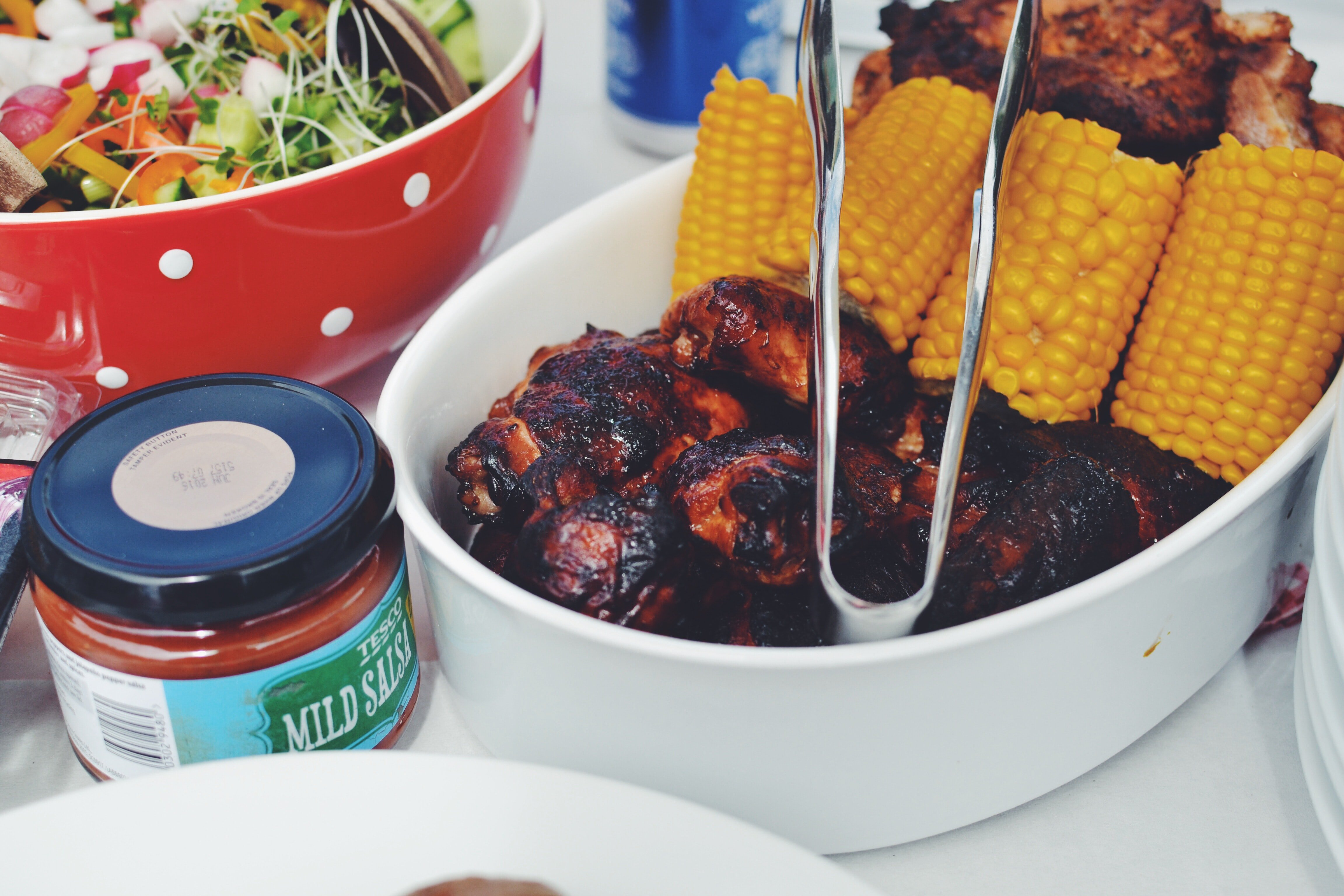 Close up of chicken drumsticks and corn on the cob