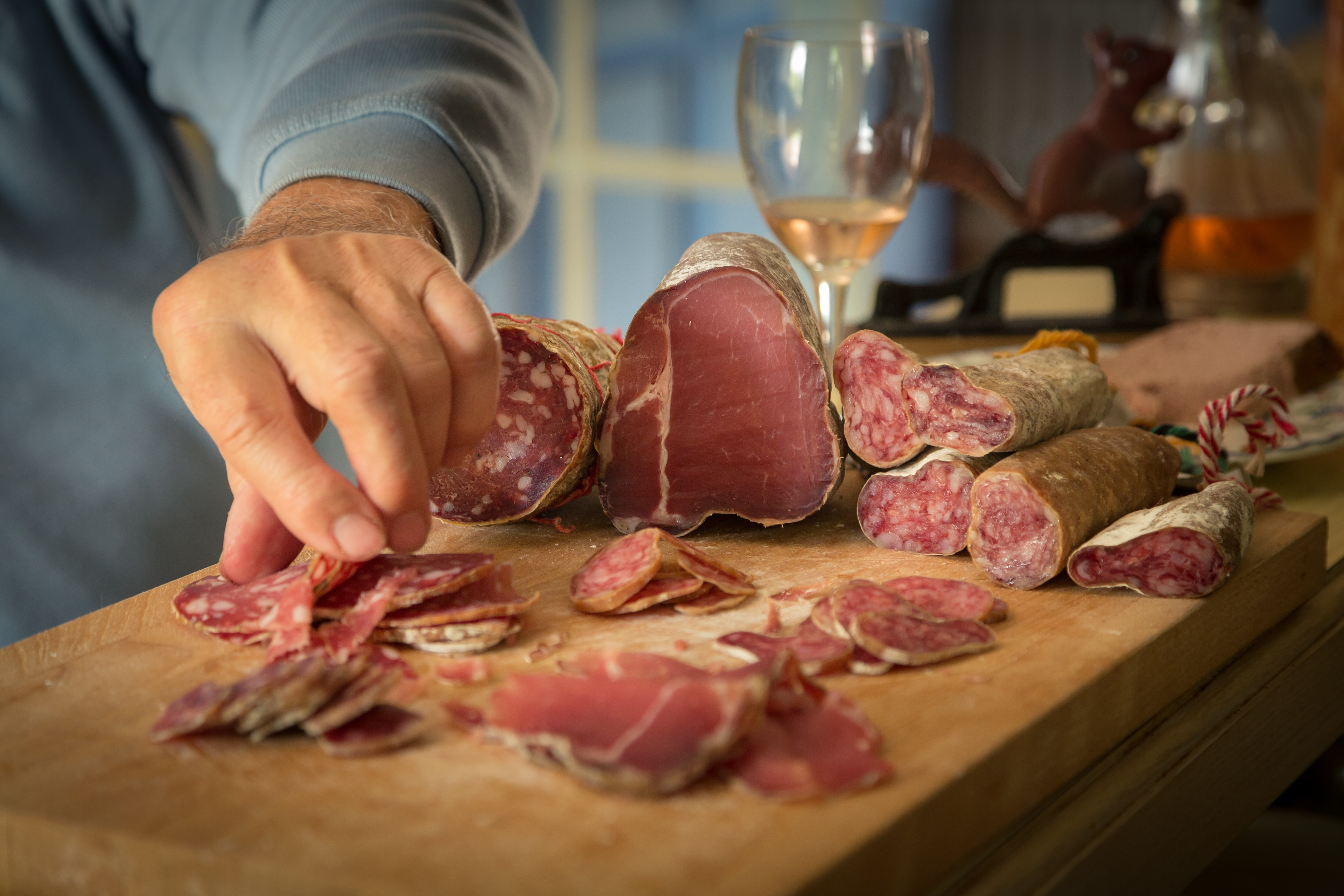 Charcuterie meats being cut on a wooden board
